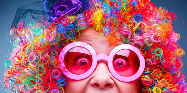 Fasnacht - Frau mit frabiger Perücke und riesiger rosa Brille.